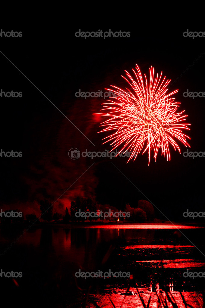 Beautiful red firework over a lake with reflections, perfect black sky as copy space for text. — Stock Photo #12445352