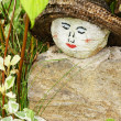 Painted face on rock garden decoration — Stock Photo