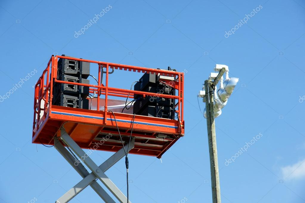 Stack of speaker equipment high in the sky on lift platform ready for outdoor concert in the park, beside lighting. — Stockfoto #13194734
