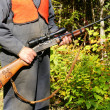 Hunter with rifle in the woods - Stock Photo