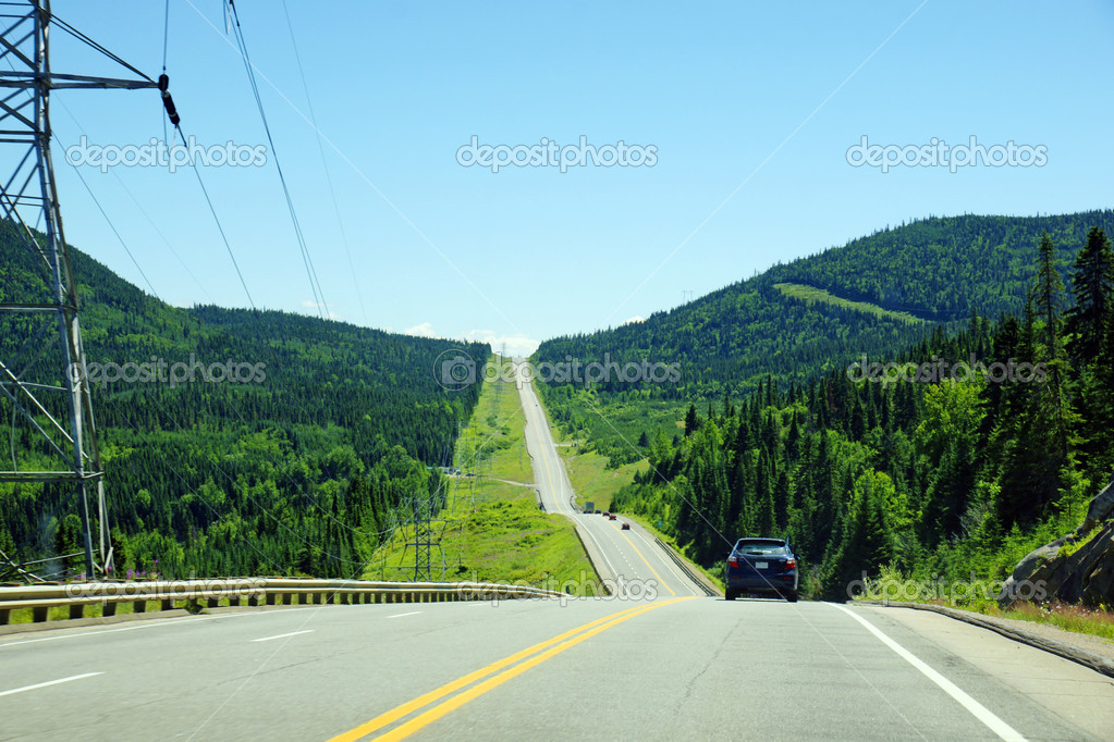 Mountain road in black spruce boreal forest of Canada with electric pilones close by, parc des laurentides, quebec. — Stock Photo #14050820