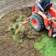 Tractor emoving turf - Stock Photo