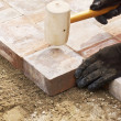 Using a mallet to set paver — Stock Photo