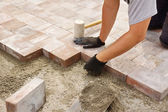 Worker installing paver — Stock Photo