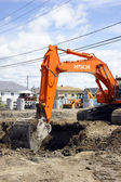 Hitachi orange digger and deep hole — Stok fotoğraf