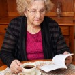 Senior with tea reading — Stock Photo