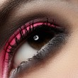 Elegance close-up of female eye with celebratory bright color eyeshadow. Macro shot of beautiful woman's face part. Wellness, cosmetics and make-up. Vibrant pink & black colours in visage — Stock Photo