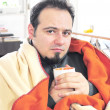 Man with fever holding cup of tea - Stockfoto