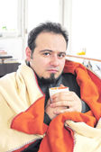 Man with fever holding cup of tea — Stock Photo
