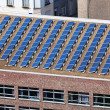 Solar panels on building roof - Stock Photo