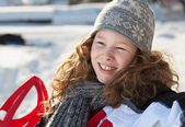 Smiling blond girl in winter park — Stockfoto