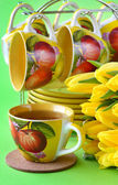 Tea cups and yellow tulips — Stock Photo