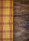 Tablecloth on wooden table background — Stock Photo