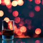 Glass of whiskey on bokeh background — Stock Photo