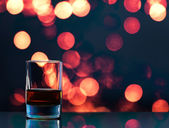Glass of whiskey on bokeh background — Stock Photo