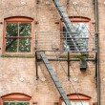 Black Fire Escape on Red Brick Building — Stock Photo #13539578