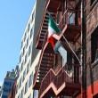Stock Photo: Old brick building with Irish flag on fire escape