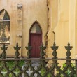 Wrought Iron Fence Before Red Church Door - Stock Photo