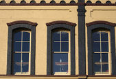 Recortar tres ventanas con ladrillo oscuro — Foto de Stock