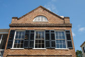 Three Windows with Black Shutters in Old Brick — Stock Photo