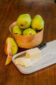 Bowl of Pears with Sliced Cheese and One Cut Pear — Stock Photo