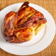 Roast Chicken Angled on White Plate and Bamboo Mat — Stock Photo