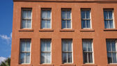 Windows in Old Red Stucco Building — Stock Photo