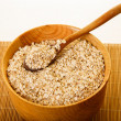 Oats in Wood Bowl on Bamboo Mat — Stock Photo