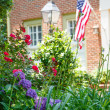 American Flag on Brick Home Behind Garden — Stock Photo #27504471