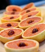 Red Grapefruit Halves with Grape Garnish — Stock Photo