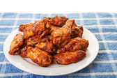 White Plate of Chicken Wings on Blue Mat — Stock Photo