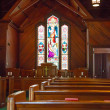 Wood Pews and Stained Glass in Small Church — Stock Photo #28679347