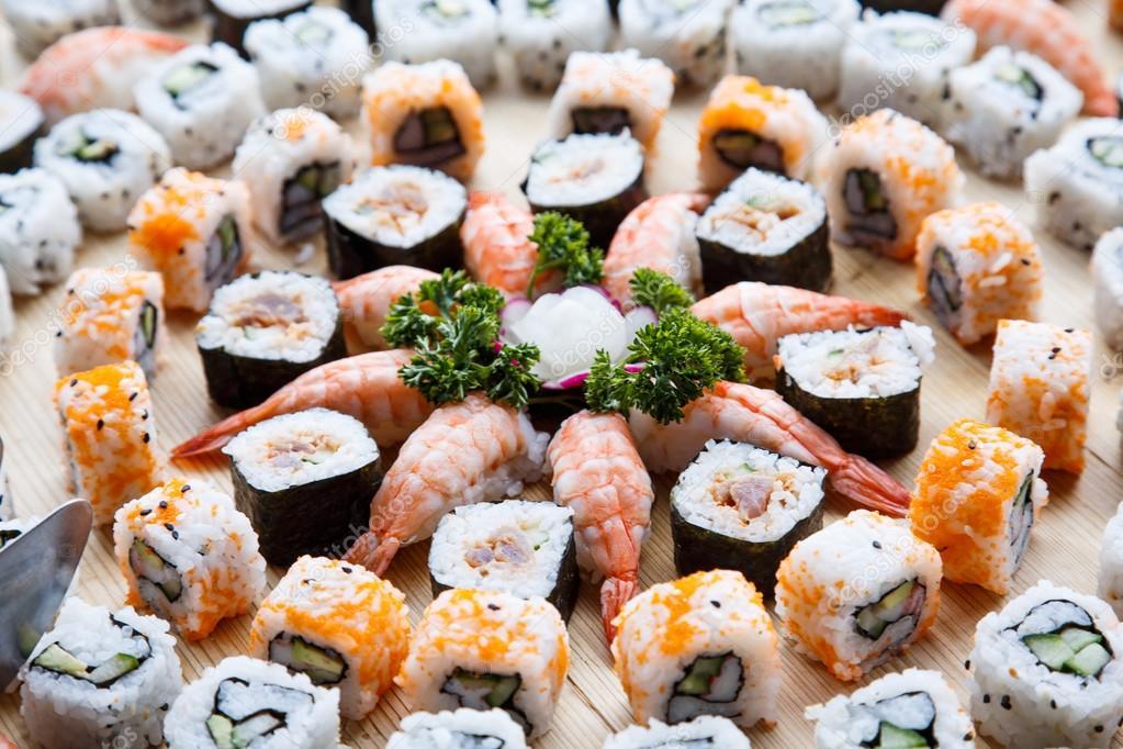Una bandeja de sushi fresco, camarones y california rolls\u2014 Foto de dbvirago