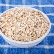 Dry Oatmeal in White Bowl on Blue Towel — Stock Photo