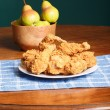 Fried Chicken on Blue Placemat and Bowl of Pears — Stock Photo