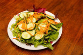 Salad with Cucumbers and Carrots on Wood Table — Stock Photo