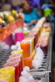 Plastic Cups of Colorful Fruit Juices in a Market — Stock Photo