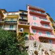 Yellow and Pink Condos Over Stone Wall — Stock Photo