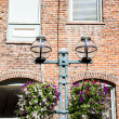 Flower Baskets on Old Lamppost by Brick Wall — Stock Photo #39307483