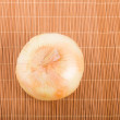 Stock Photo: Whole Yellow Onion on Bamboo Placemat
