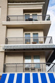 Condo Balconies Over Blue and White Awning — Stock Photo