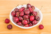 Bowl of Cherries with Three on Table — Stock Photo