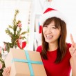 Excited Asian getting her Christmas present - Stockfoto
