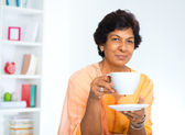 Mature Indian woman drinking coffee — Stock Photo