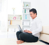Asian man browsing internet — Stock Photo