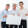 Asian business team holding a blank banner — Stock Photo