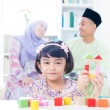 Muslim child building toy wooden house. — Stockfoto #18079873