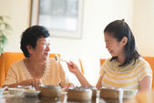 Feeding senior parent food — Stock Photo