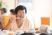 Hochrangige asiatische frau essen gemüse — Stockfoto