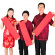 Asian Chinese family holding red spring couplets — Stock Photo